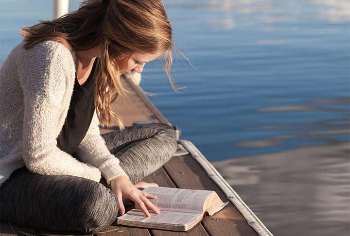 水辺で本を読んでいる女性